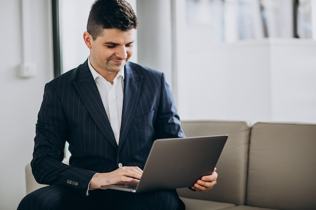 Young handsome business man working on computer on a sofa in office Free Photo