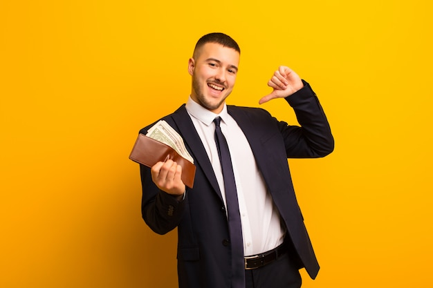 Young handsome businessman  against flat background money concept Premium Photo
