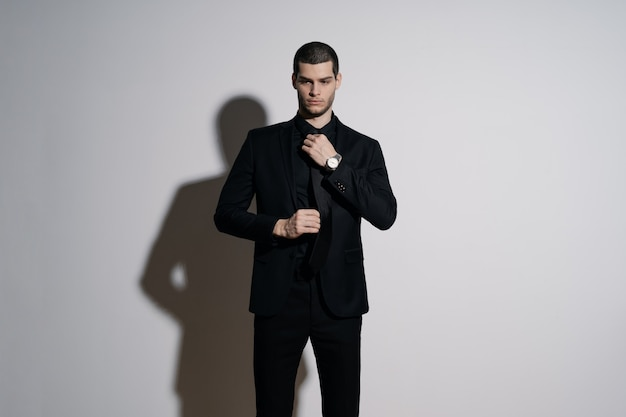 Young handsome businessman in black shirt and black suit Free Photo