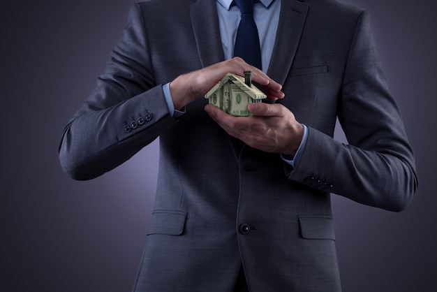 Young handsome businessman holding a house Premium Photo