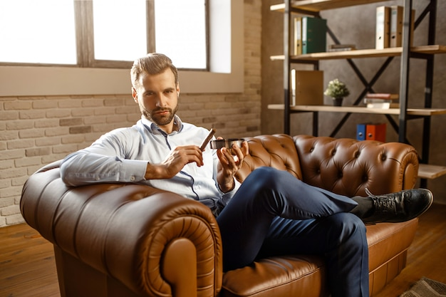 Young handsome businessman in smoke cigar his own office. he sit on sofa and hold it with ash-pot. guy look on camera with confidence. brutal and sexy. Premium Photo