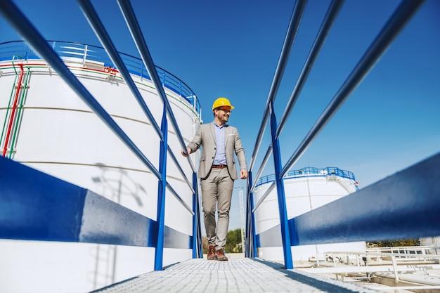 Молодой красивый кавказский бизнесмен в костюме и с шлемом на голове идя на мост и смотря его рафинадный завод. Premium Фотографии