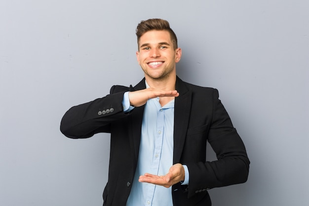 Young handsome caucasian man holding something with both hands, product presentation. Premium Photo