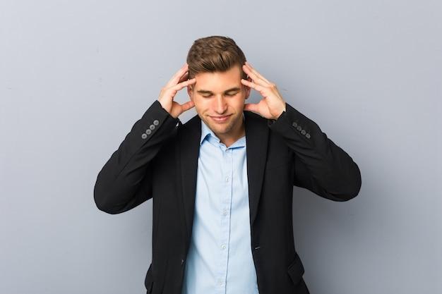 Молодой красивый кавказский человек трогательно висков и головной боли. Premium Фотографии