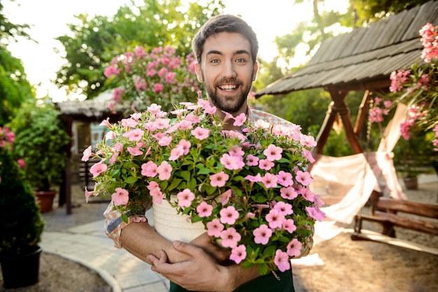 Young handsome cheerful gardener smiling, holding big pot with flowers Free Photo