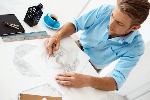 若いハンサムな自信を持って物思いに沈んだ実業家鉛筆画の肖像画でテーブルに座っている白い近代的なオフィスの内壁。 無料写真