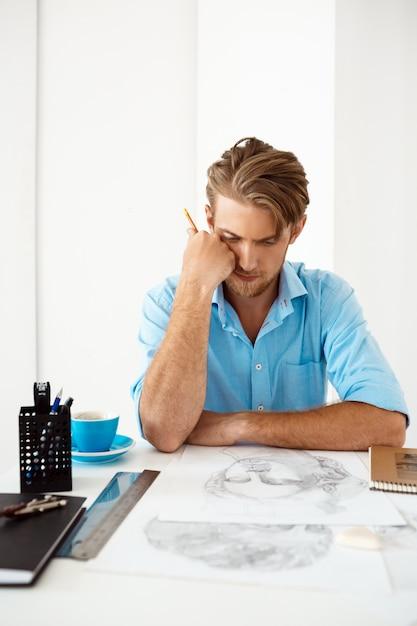 Giovane uomo d'affari pensieroso sicuro bello che si siede alla tavola che pensa sopra il ritratto del disegno a matita. interno di ufficio moderno bianco. Foto Gratuite