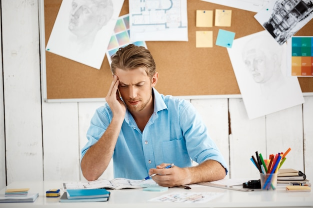 Young handsome confident pensive businessman working sitting at table thinking over notepad. white modern office interior Free Photo