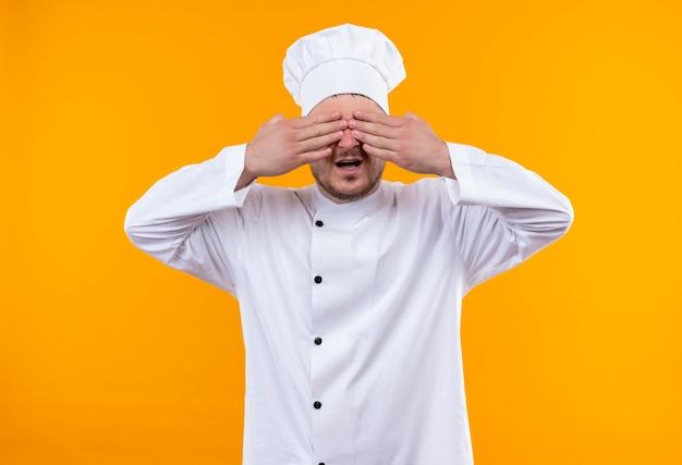 Giovane cuoco bello in uniforme del cuoco unico che chiude gli occhi con le mani con la bocca aperta isolata sullo spazio arancione Foto Gratuite