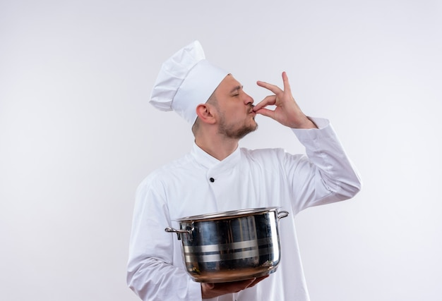 Young handsome cook in chef uniform holding boiler and doing tasty gesture on isolated white space Free Photo