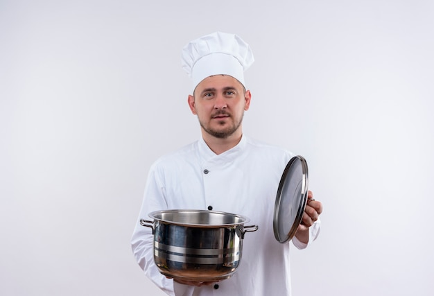 Young handsome cook in chef uniform holding boiler and its cover looking  on isolated white space Free Photo