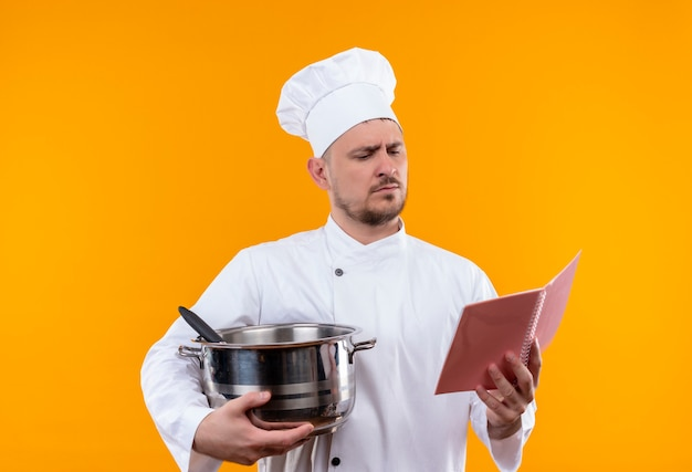 Young handsome cook in chef uniform holding boiler and note pad and looking at note pad on isolated orange space Free Photo