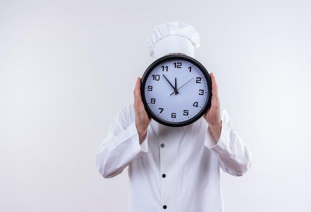Giovane cuoco bello in orologio della holding dell'uniforme dello chef e nascondersi dietro di esso isolato su uno spazio bianco Foto Gratuite