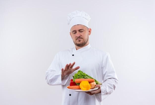 Giovane cuoco bello nel piatto della tenuta dell'uniforme del cuoco unico con le verdure che li guarda e che tiene la mano sopra di loro su uno spazio bianco isolato Foto Gratuite