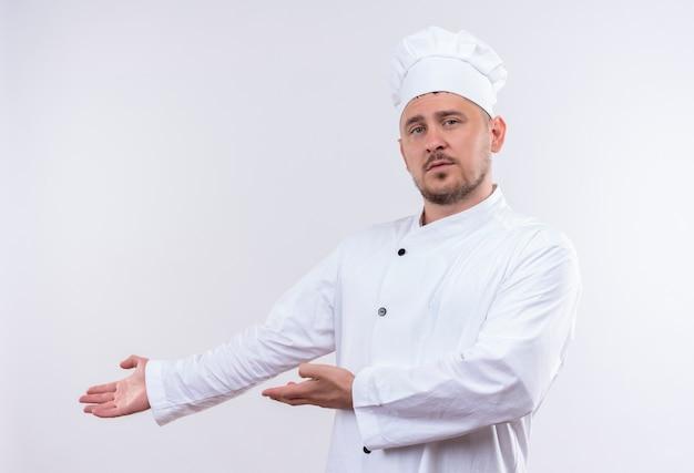 Giovane cuoco bello in uniforme del cuoco unico che indica con le mani al lato che osserva isolato su spazio bianco Foto Gratuite