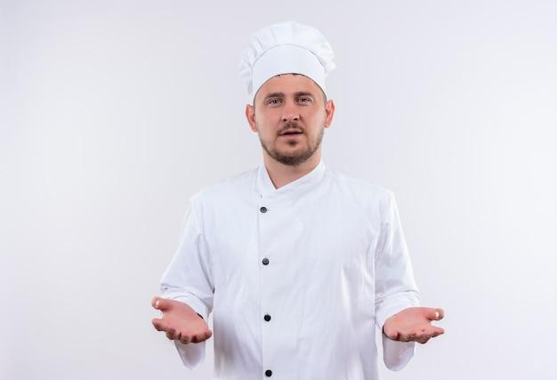 Giovane cuoco bello in uniforme del cuoco unico che mostra le mani vuote che sembrano isolate sullo spazio bianco Foto Gratuite