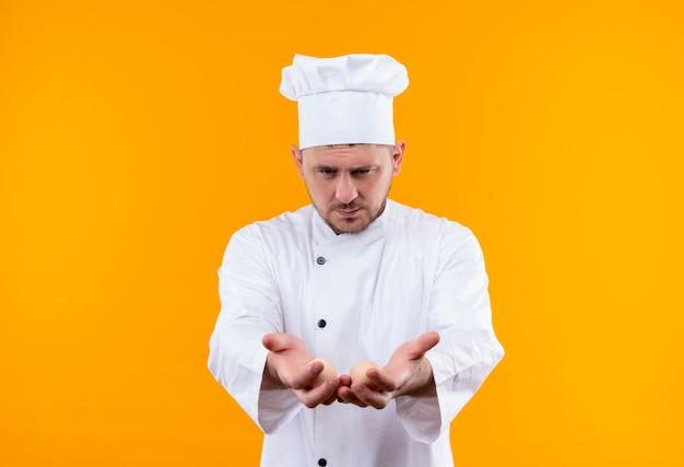 Giovane cuoco bello in uniforme del cuoco unico che allunga e che mostra le mani vuote e li guarda isolati sullo spazio arancione Foto Gratuite
