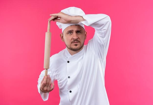 Молодой красивый повар в униформе шеф-повара держит скалку, глядя изолированно на розовом пространстве Бесплатные Фотографии