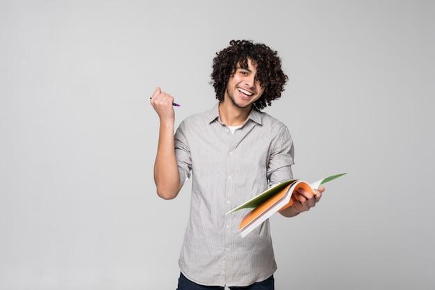 Молодой красивый вьющийся человек студента с тетрадями над изолированный на белой стене Бесплатные Фотографии