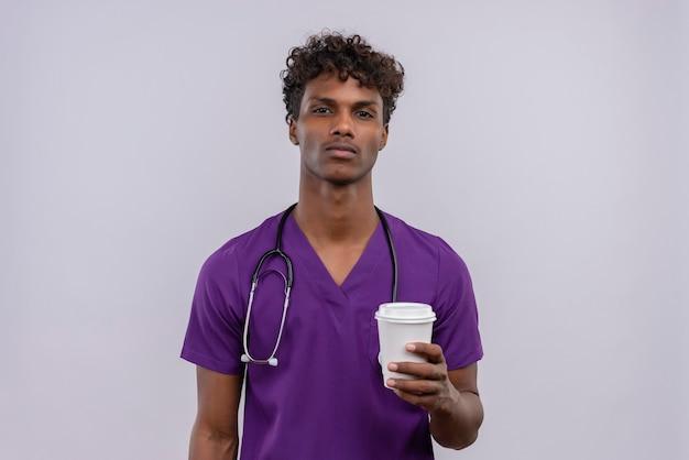 Un giovane medico dalla carnagione scura bello con capelli ricci che porta l'uniforme viola con lo stetoscopio che tiene la tazza di caffè di carta Foto Gratuite