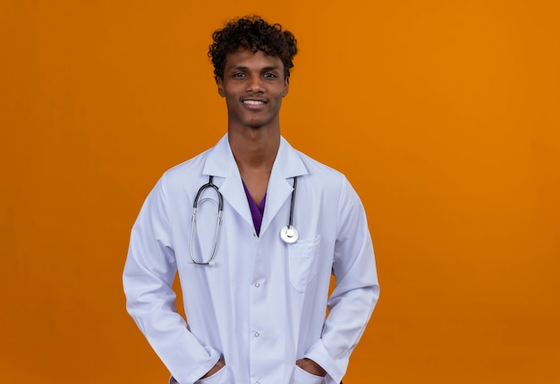 A young handsome dark-skinned man with curly hair wearing white coat with stethoscope putting hands on pockets Free Photo