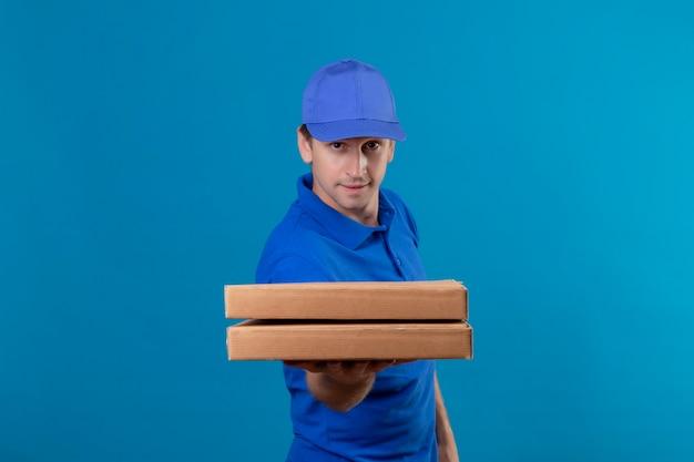 青い制服を着た若いハンサムな配達人と青い壁の上に立っている顔に自信を持って笑顔でピザの箱を保持しているキャップ 無料写真