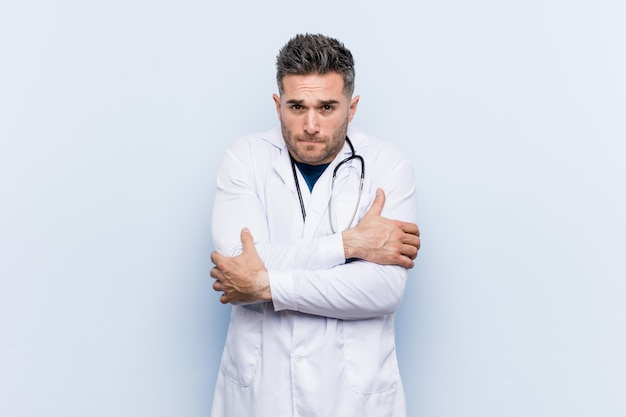 Young handsome doctor man going cold due to low temperature or a sickness Premium Photo