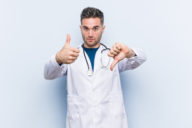 Young handsome doctor man showing thumbs up and thumbs down, difficult choose concept Premium Photo