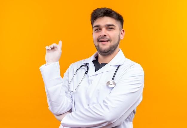 Молодой красивый врач в белом медицинском халате, белые медицинские перчатки и стетоскоп, глядя с учительским лицом, указывающим назад, с указательным пальцем, стоящим над оранжевой стеной Бесплатные Фотографии