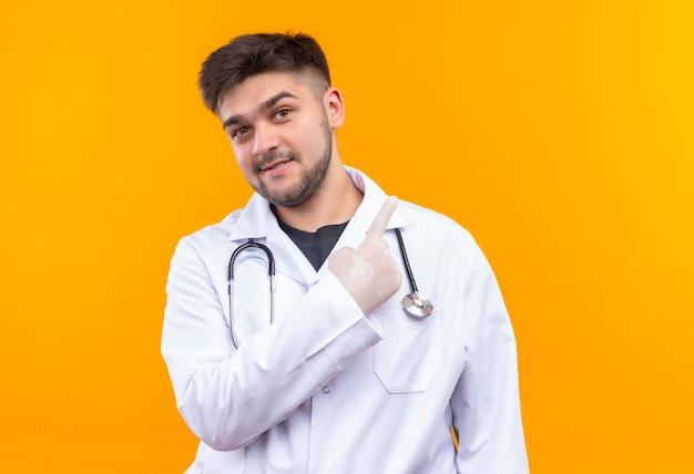 Молодой красивый врач в белом медицинском халате, белые медицинские перчатки и стетоскоп, указывая вверх с указательным пальцем, стоящим над оранжевой стеной Бесплатные Фотографии