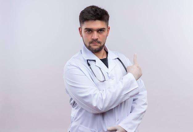 Молодой красивый врач в белом медицинском халате, белые медицинские перчатки и стетоскоп, серьезно глядя, показывая назад указательным пальцем, стоящим над белой стеной Бесплатные Фотографии