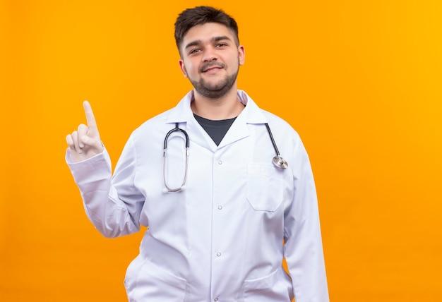 Молодой красивый врач в белом медицинском халате, белые медицинские перчатки и стетоскоп, улыбаясь, указывая вверх указательным пальцем, стоя над оранжевой стеной Бесплатные Фотографии