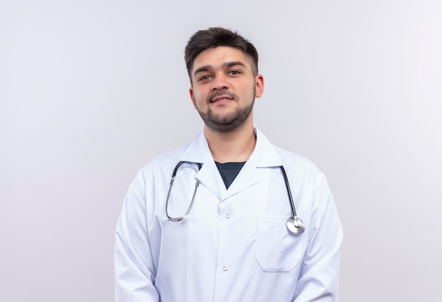 Молодой красивый врач в белом медицинском халате, белые медицинские перчатки и стетоскоп, улыбаясь, стоя над белой стеной Бесплатные Фотографии