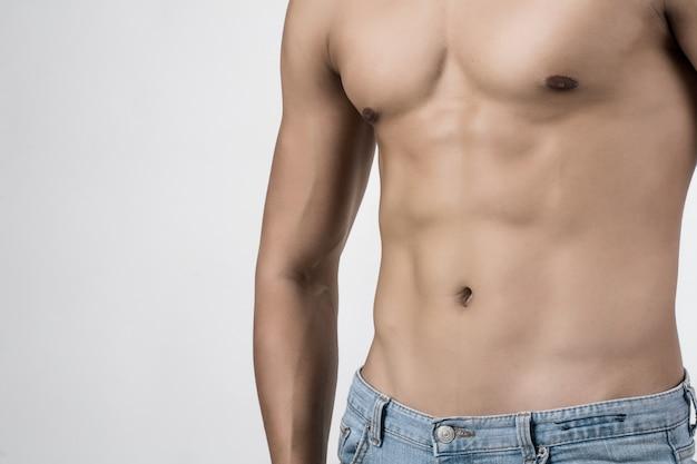若いハンサムな男は、彼の筋肉をcopyspaceと白い背景に隔離されているポーズ。 無料写真