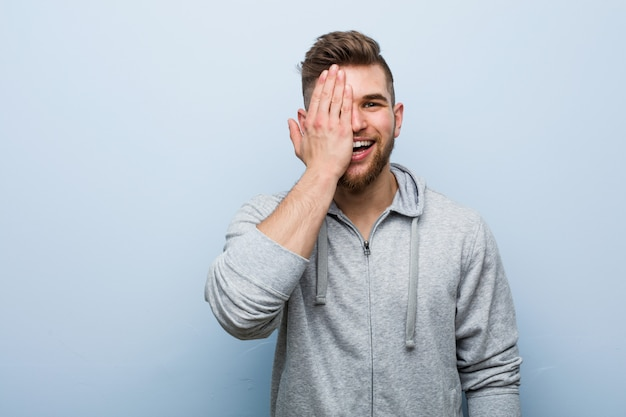 Young handsome fitness man having fun covering half of face with palm. Premium Photo