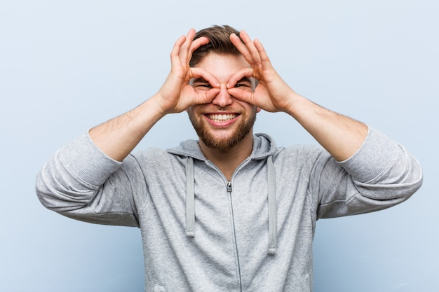 Young handsome fitness man showing okay sign over eyes Premium Photo