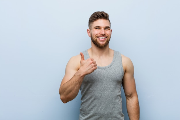 Young handsome fitness man smiling and raising thumb up Premium Photo