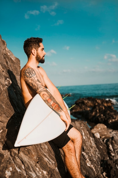 Young handsome guy holding surf board near stones Free Photo
