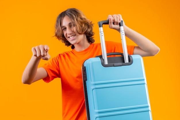 Молодой красивый парень в оранжевой футболке держит дорожный чемодан, указывая пальцем на камеру, весело улыбаясь, выглядит счастливым и позитивным, стоя на желтом фоне Бесплатные Фотографии