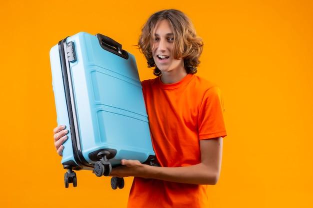 Молодой красивый парень в оранжевой футболке держит дорожный чемодан позитивным и счастливым, улыбаясь, весело стоя на желтом фоне Бесплатные Фотографии