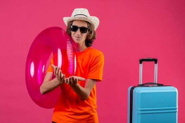 お金を求めて一緒に折り畳まれた手で旅行スーツケースで立っているインフレータブルリングを保持している黒いサングラスをかけているオレンジ色のtシャツの若いハンサムな男 無料写真