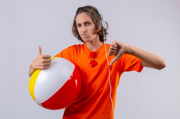 Молодой красивый парень в оранжевой футболке с наушниками, держащий надувной мяч, недоволен, показывая большие пальцы вверх и вниз стоя Бесплатные Фотографии