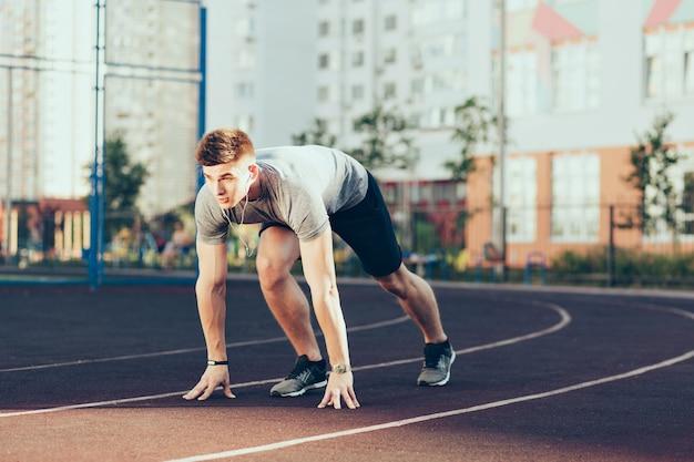スタジアムで朝の若いハンサムな男。彼はスポーツウェアを着て、ヘッドフォンで音楽を聞いて、走りに行きます。 無料写真