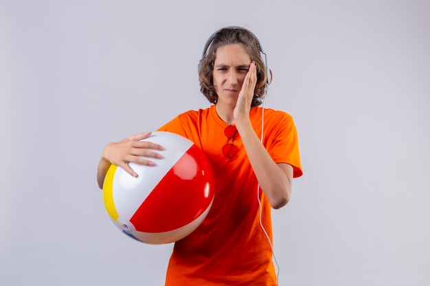 Young handsome guy in orange t-shirt holding inflatable ball with headphones looking unwell touching cheek having toothache standing over white background Free Photo