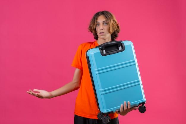 Giovane ragazzo bello in maglietta arancione che tiene la valigia da viaggio all'oscuro e confuso non avendo risposta diffondendo le mani in piedi su sfondo rosa Foto Gratuite