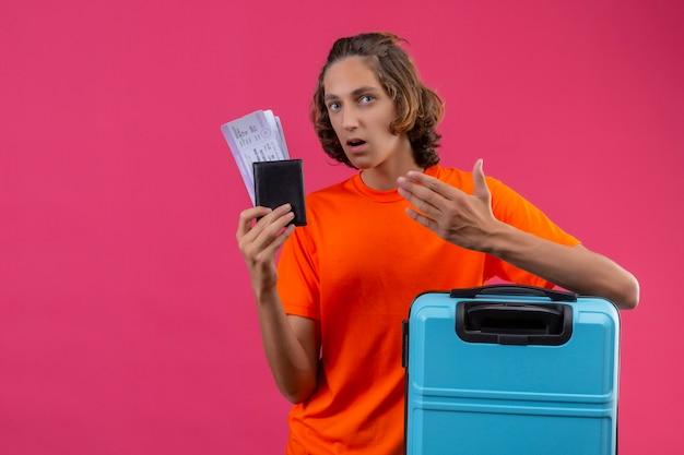 Giovane ragazzo bello in maglietta arancio che sta con i biglietti aerei della tenuta della valigia di viaggio che sembrano sconcertanti con il braccio alzato Foto Gratuite