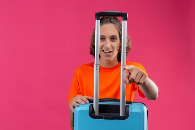 Giovane ragazzo bello in maglietta arancione in piedi con la valigia da viaggio che punta con il dito alla fotocamera sorridente con la faccia felice su sfondo rosa Foto Gratuite