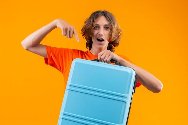 Giovane bel ragazzo in maglietta arancione in piedi con la valigia da viaggio che punta con il dito ad esso guardando fiducioso e felice su sfondo giallo Foto Gratuite
