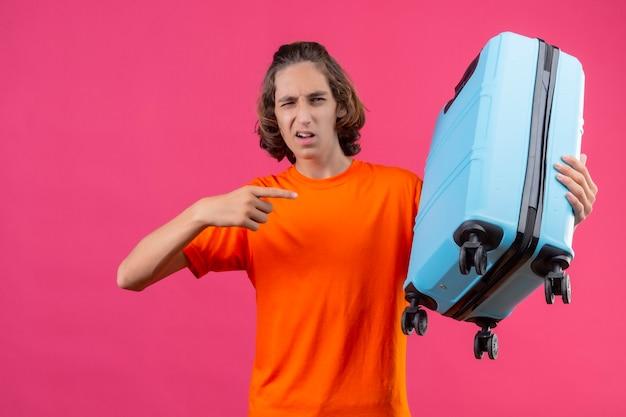 Giovane ragazzo bello in maglietta arancione in piedi con la valigia da viaggio che punta con il dito ammiccante guardando fiducioso su sfondo rosa Foto Gratuite