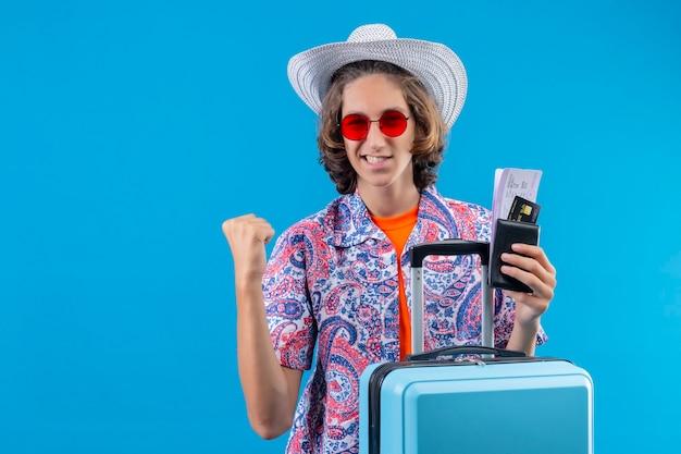 Giovane bel ragazzo in cappello estivo indossando occhiali da sole rossi azienda valigia di viaggio e biglietti aerei cercando uscito e felice alzando il pugno dopo una vittoria che rallegra il suo successo in piedi su ba blu Foto Gratuite